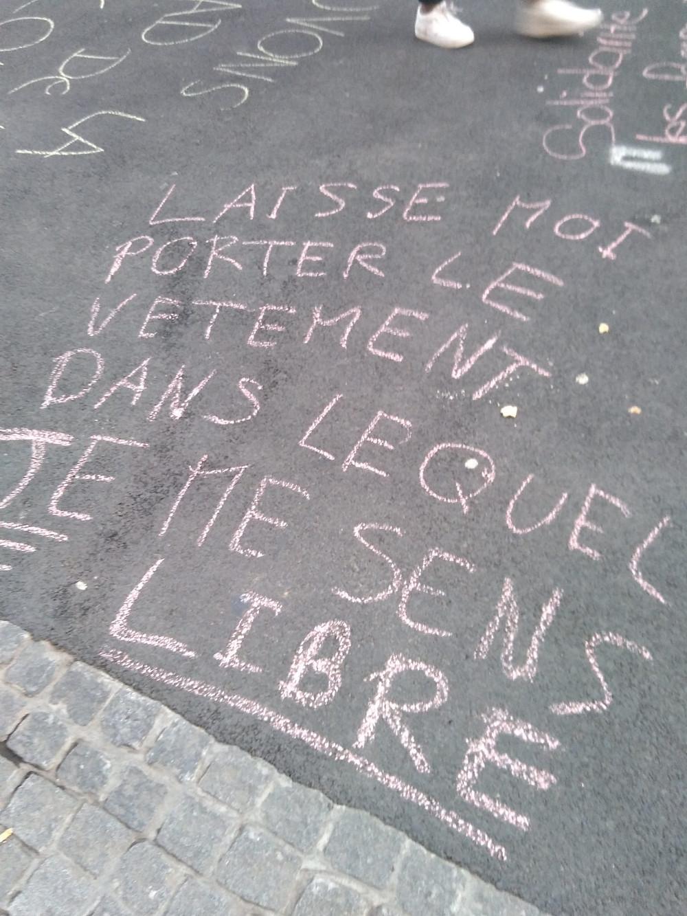 Slogan écrit à la craie à l'espace Espacité, à la Chaux-de-Fonds. Le slogan : Laisse moi porter le vêtement dans lequel JE me sens libre.