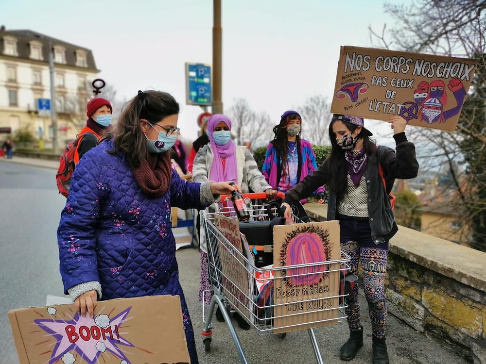 Les femmes défilent depuis la gare, avec un caddie. Dans ce caddie, se trouve une peinture de vulve poilue. L'une d'elle tient une pancarte : Nos corps, nos choix, pas ceux de l'état.