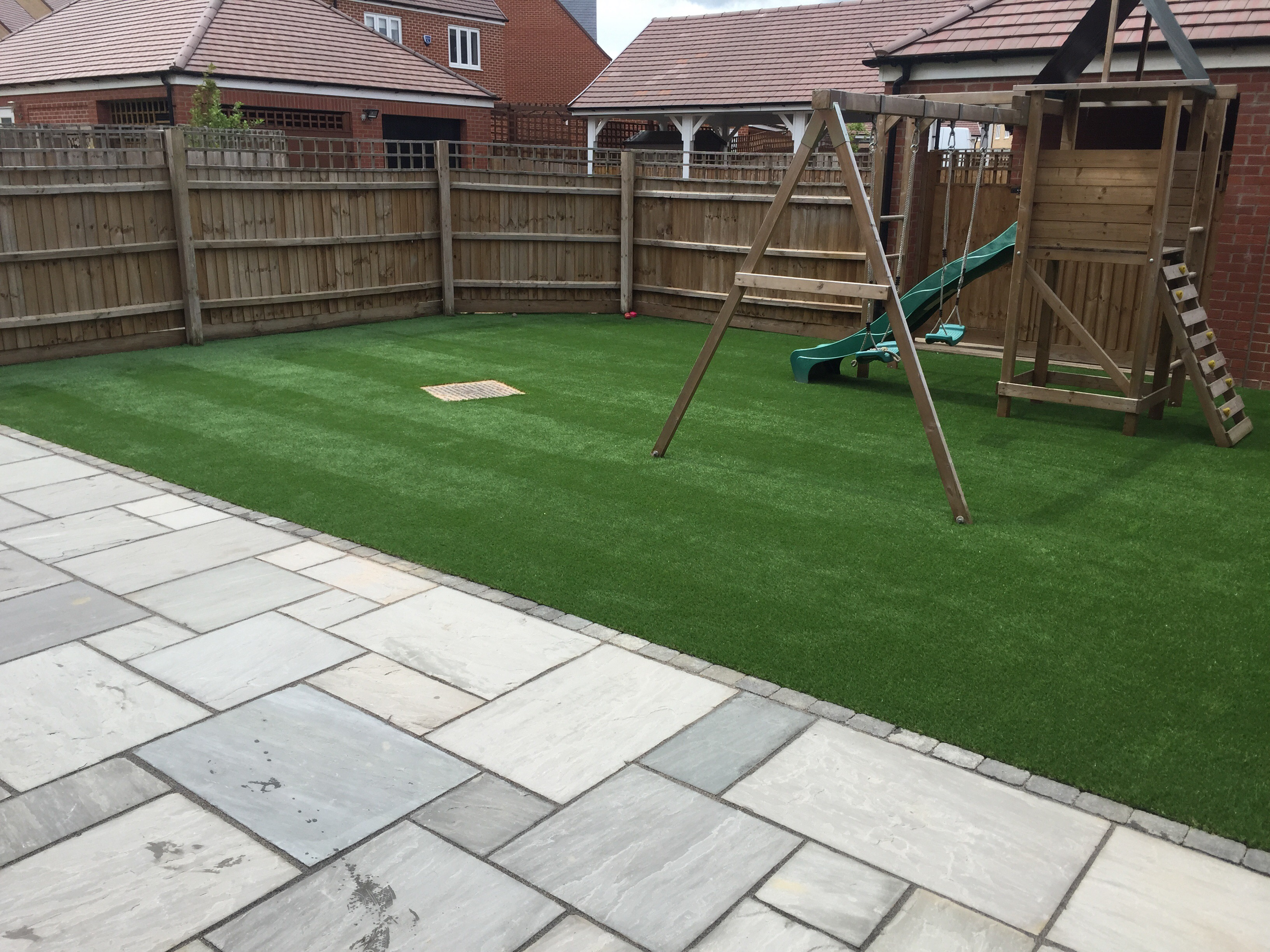 Sandstone patio and artificial lawn