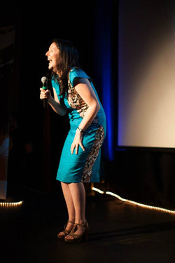Esther Coleman-Hawkins standing on a stage holding a microphone and laughing