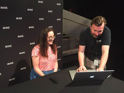 Esther Coleman-Hawkins sitting at a computer at an ACMI event, a man is standing next to her using t