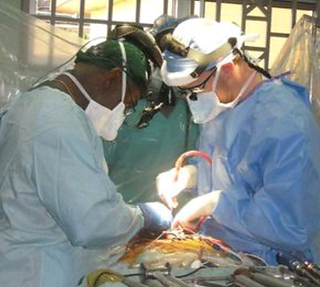 Dr. Oheneba Boachei operating with Dr. Benjamin Bjerke on a severe spinal deformity in Ghana, Africa
