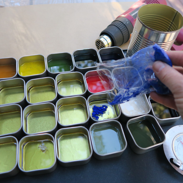 Mixing the pigments with the melted encaustic medium.