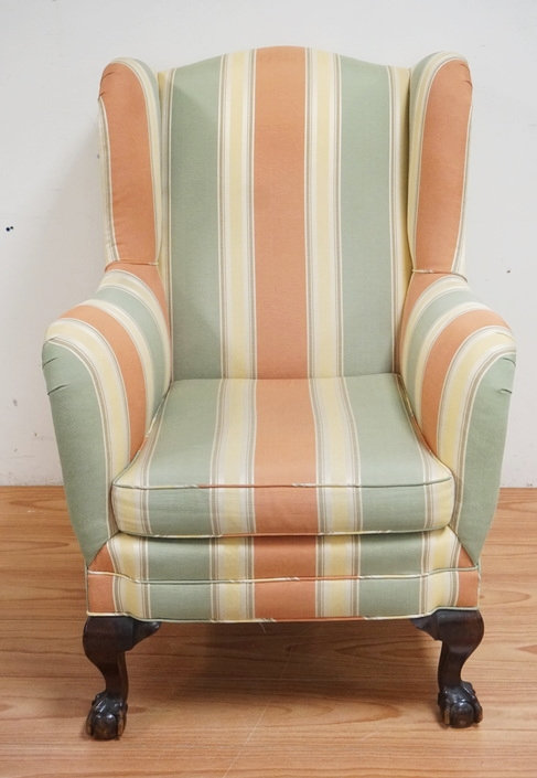 UPHOLSTERED WING CHAIR WITH CARVED BALL & CLAW FEET. 44 INCHES HIGH. 32 INCHES W