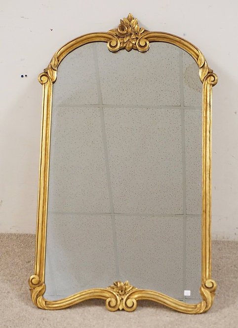 WALL MIRROR WITH A CARVED GOLD GILT FRAME. 26 1/2 X 44 INCHES.