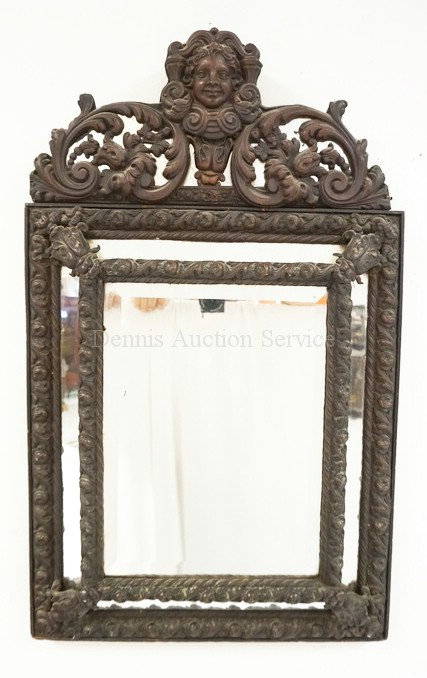 MIRROR WITH AN ORNATE METAL FRAME. 29 1/2 X 18 INCHES.