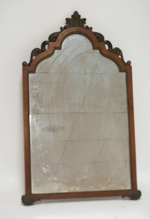 WALNUT MIRROR WITH A CARVED CREST. 26 1/4 INCHES HIGH.