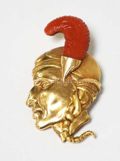 18K GOLD (19.3 TOTAL DWT) BROOCH IN THE FORM OF A BUST WITH A CARVED CORAL FEATH