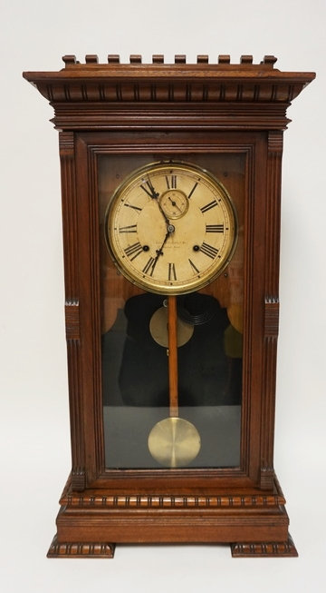 GILBERT *LATONA* SHELF CLOCK WITH A CARVED WALNIT CASE. 30 INCHES HIGH. 15 3/4 I
