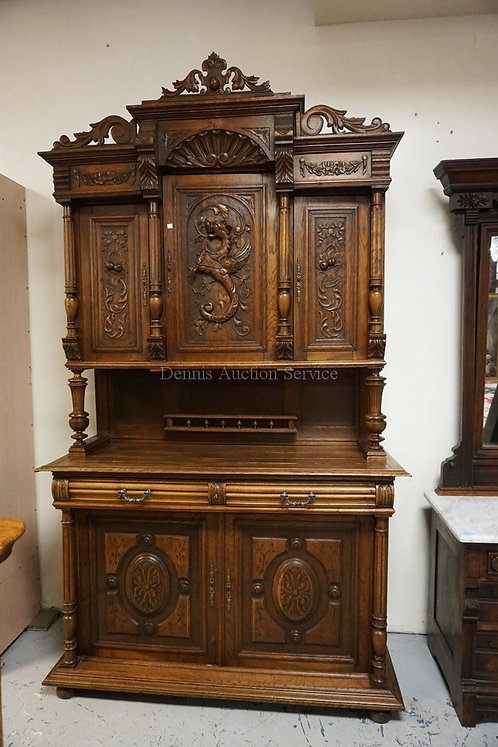 CARVED ENGLISH OAK SIDEBOARD WITH A CABINET TOP. HEAVILY CARVED DOORS WITH THE C