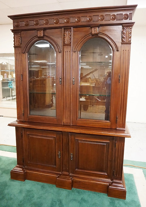 CARVED WALNUT TWO PIECE CABINET WITH GLASS DOORS OPENING TO GLASS SHELVES OVER A