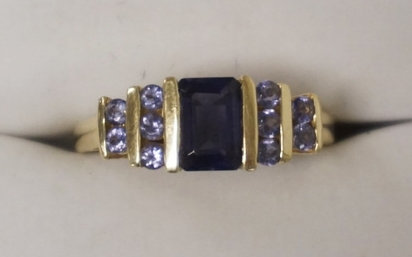 14K AMETHYST & DIAMOND RING. A CENTRAL AMETHYST FLANKED BY A TOTAL OF 10 ROUND D