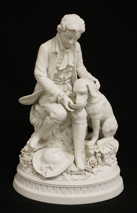 BISQUE PORCELAIN FIGURAL GROUP OF A BOY FEEDING A DOG. 15 1/4 INCHES HIGH.