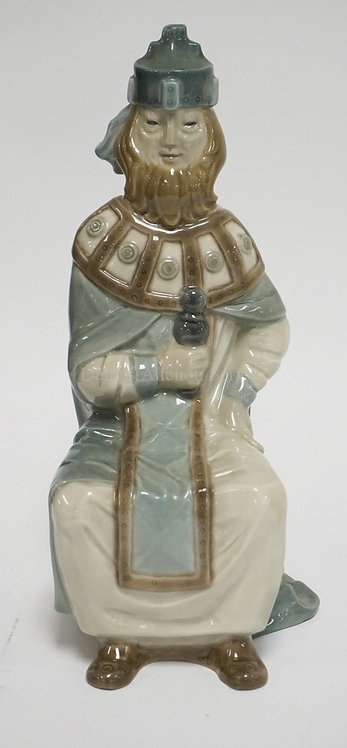 LLADRO PORCELAIN FIGURE OF A SEATED MAN. 11 INCHES HIGH.
