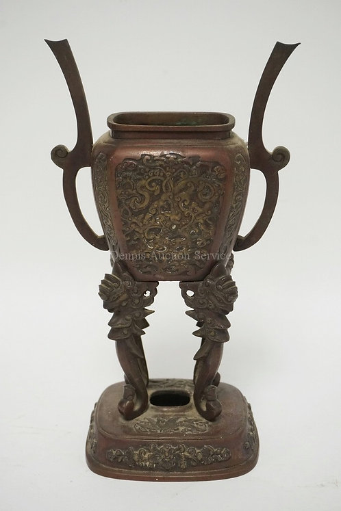 ASIAN BRONZE URN WITH RELIEF DECORATIONS OF DRAGONS WITH FIGURAL SUPPORTS. 11 1/
