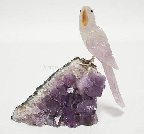 CARVED STONE BIRD MOUNTED ON AN AMETHYST GEODE SECTION. 5 3/4 INCHES HIGH.