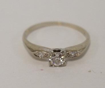 18K AND DIAMOND RING. MAIN DIAMOND IS .2C ALSO HAS 2 SIDE DIAMONDS