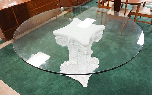 DINING TABLE WITH AN ORNATE PLASTER COLUMN FORM BASE AND A 60 INCH GLASS TOP.