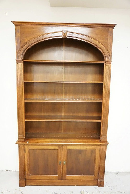 WALNUT BOOKCASE WITH AN ARCHED OPENING AND FLUTED COLUMNS. 2 DOOR CABINET BELOW.