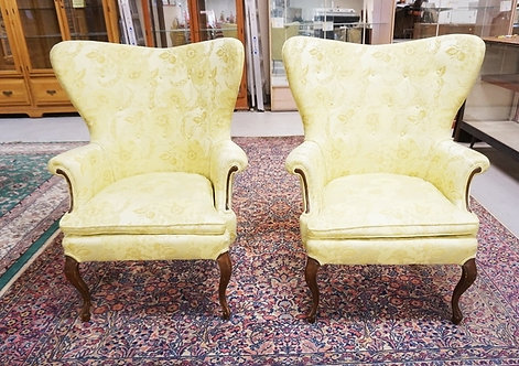 PAIR OF UPHOLSTERED WING CHAIRS IN FLORAL YELLOW UPHOLSTERY.