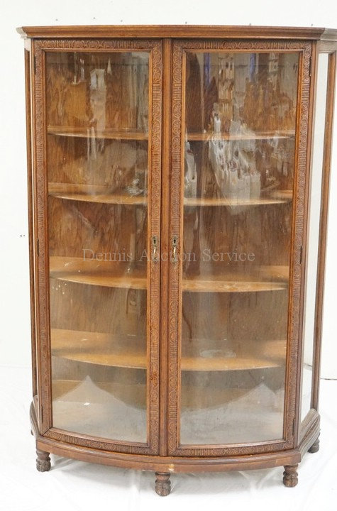 CARVED OAK BOW FRONT CHINA CABINET. 66 1/2 INCHES HIGH. 45 INCHES WIDE.