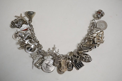 STERLING SILVER CHARM BRACELET WITH MANY CHARMS. 2.99 TROY OZ. IT APPEARS THAT A