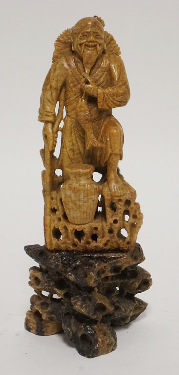 CARVED SOAPSTONE FIGURE OF AN ASIAN MAN WITH A FISH. 7 5/8 INCHES HIGH.