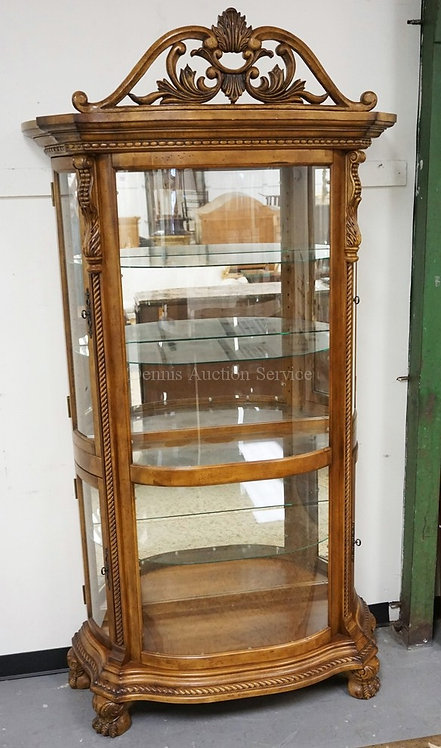 CARVED CURIO CABINET WITH GLASS SHELVES, A MIRRORED BACK, AND A LIGHTED INTERIOR