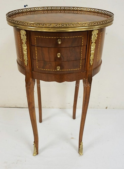 OVAL 3 DRAWER STAND DECORATED WITH INLAY, ORMOLU, AND A BRASS GALLERY. 28 1/2 IN