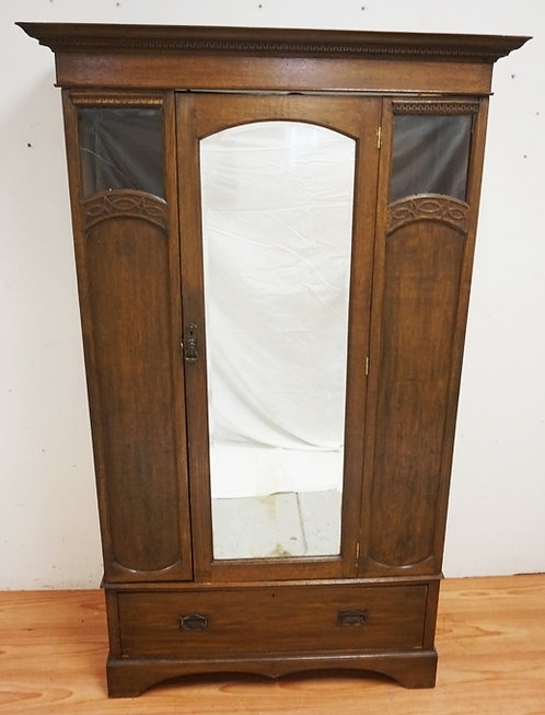 OAK ARMOIRE WITH A MIRRORED DOOR. ONE GLASS PANEL CRACKED AND SOME MISSING TRIM.