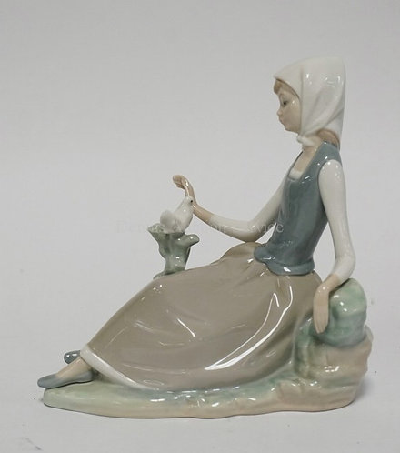 LLADRO PORCELAIN FIGURE OF A GIRL WITH A DOVE SITTING. 6 1/2 INCHES HIGH.
