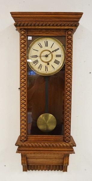 ANSONIA OAK REGULATOR CLOCK WITH CARVED TRIM. 36 X 14 1/4 INCHES.