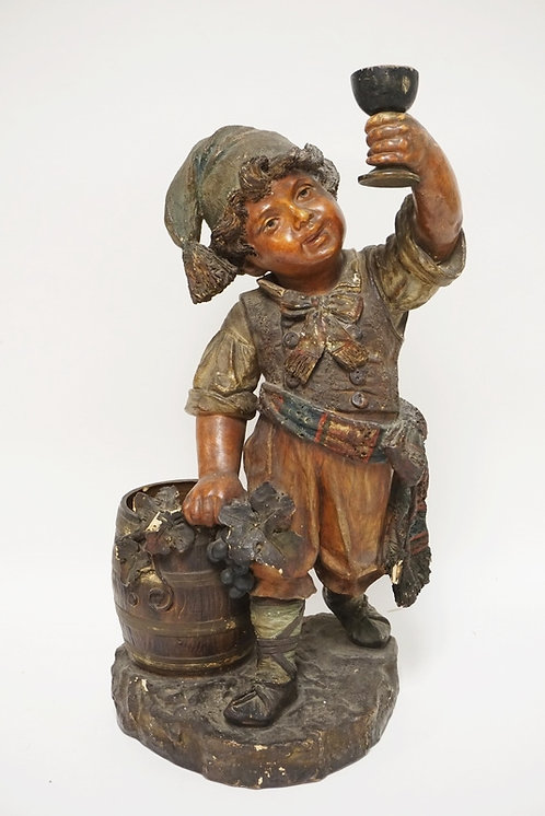 LARGE GERMAN POTTERY FIGURE OF A BOY HOLDING A CHALICE AND STANDING NEXT TO A BA