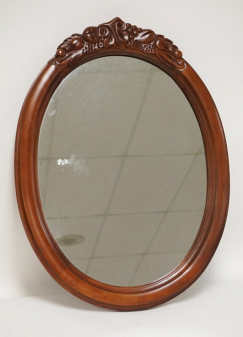 CARVED OVAL MIRROR MEASURING 29 X 21 1/2 INCHES.