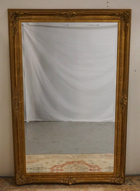 LARGE BEVELED MIRROR IN A GILT FRAME. 44 3/4 IN X 68 3/4 IN OVERALL DIMENSIONS