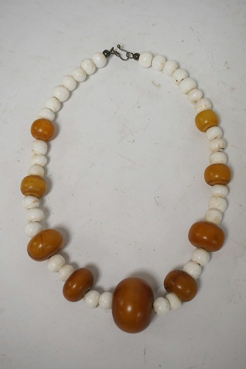 BEADED NECKLACE INCLUDING ANTIQUE AMBER AND MALA SHELL.