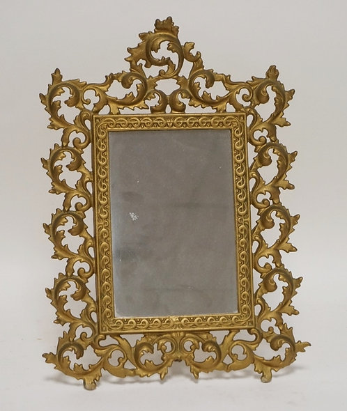 MIRROR WITH AN ORNATE CAST IRON FRAME IN GOLD PAINT. 16 1/4 X 12 INCHES.