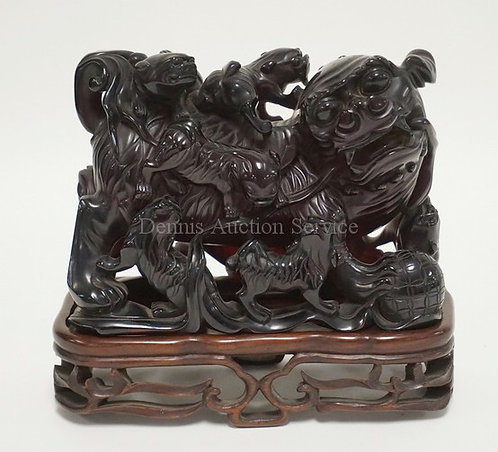 CARVED ASIAN FIGURE OF FOO DOGS ON A CARVED WOODEN STAND. 7 INCHES HIGH. 7 3/4 I