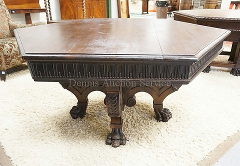 MASSIVE WALNUT DINING TABLE WITH A HEXAGONAL TOP, A CARVED SKIRT, AND A CARVED B
