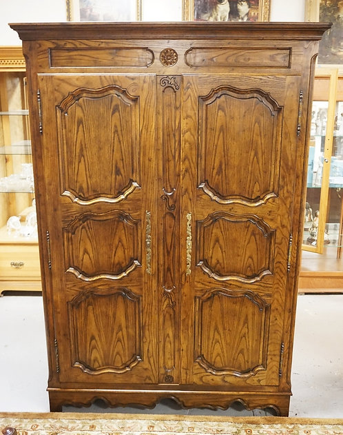 OAK ARMOIRE BY BAKER. PANELED DOORS. BRASS HARDWARE. 83 INCHES HIGH. 57 1/2 INCH