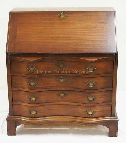 MAHOGANY SLANT FRONT DESK WITH A SERPENTINE FRONT AND A COMPARTMENTED INTERIOR.