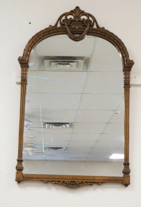 MIRROR IN A CARVED WOODEN FRAME MEASURING 40 X 25 INCHES.
