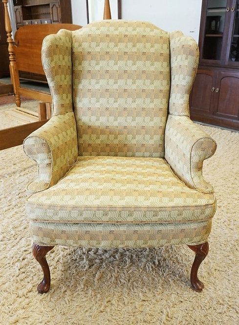 UPHOLSTERED WING CHAIR WITH CARVED LEGS. 32 INCHES WIDE. 43 1/2 INCHES HIGH.