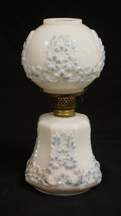 MINIATURE GLASS OIL LAMP. WHITE GLAS HAVING RAISED DESIGNS OF FLOWERS DECORATED