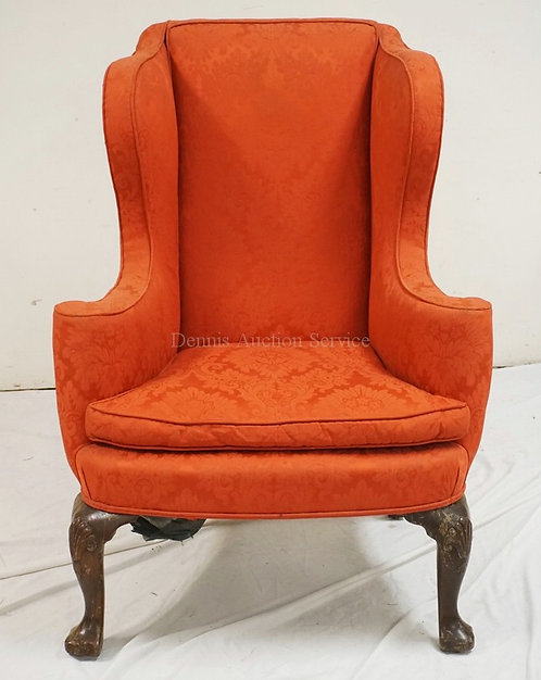 WING CHAIR WITH FLORAL UPHOLSTERY AND CARVED LEGS WITH SHELL KNEES.