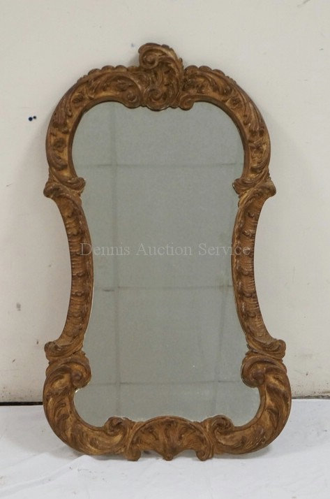 WALL MIRROR IN A CARVED WOODEN FRAME. 38 X 22 INCHES.