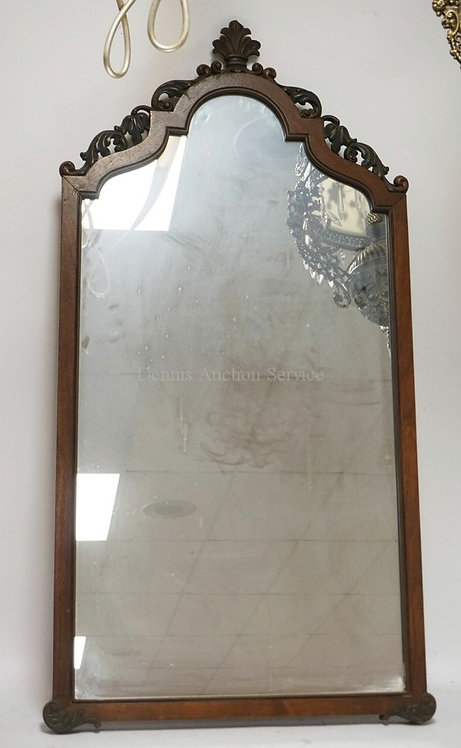 WALNUT MIRROR WITH A CARVED CREST. 44 3/4 INCHES HIGH.