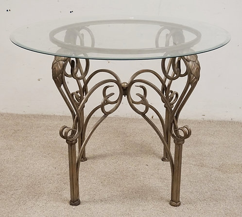 WROUGHT METAL TABLE WITH A GLASS TOP. 39 INCH DIA. 30 INCHES HIGH.