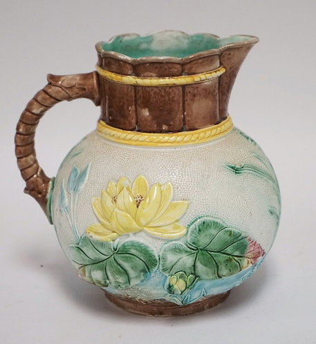 MAJOLICA POTTERY PITCHER DECORATED WITH WATER LILIES ON A STIPPLED BACKGROUND. 7