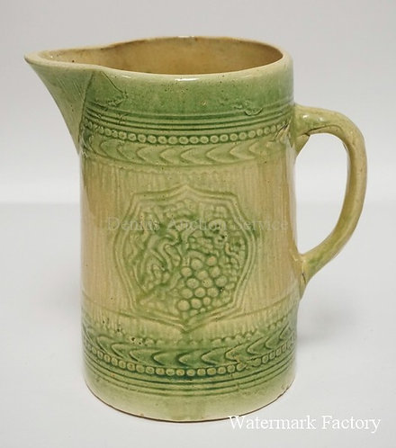 GREEN GLAZED STONEWARE PITCHER DECORATED WITH GRAPES. 8 1/2 INCHES HIGH.
